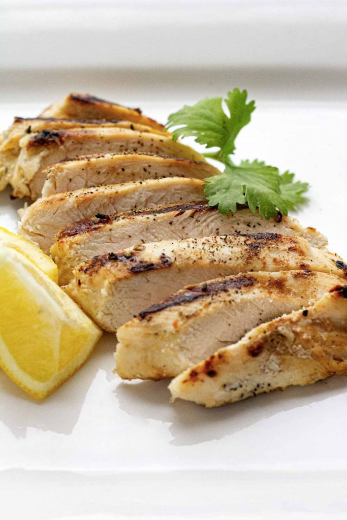 Sliced grilled chicken on white plate with lemon and parsley on the side.