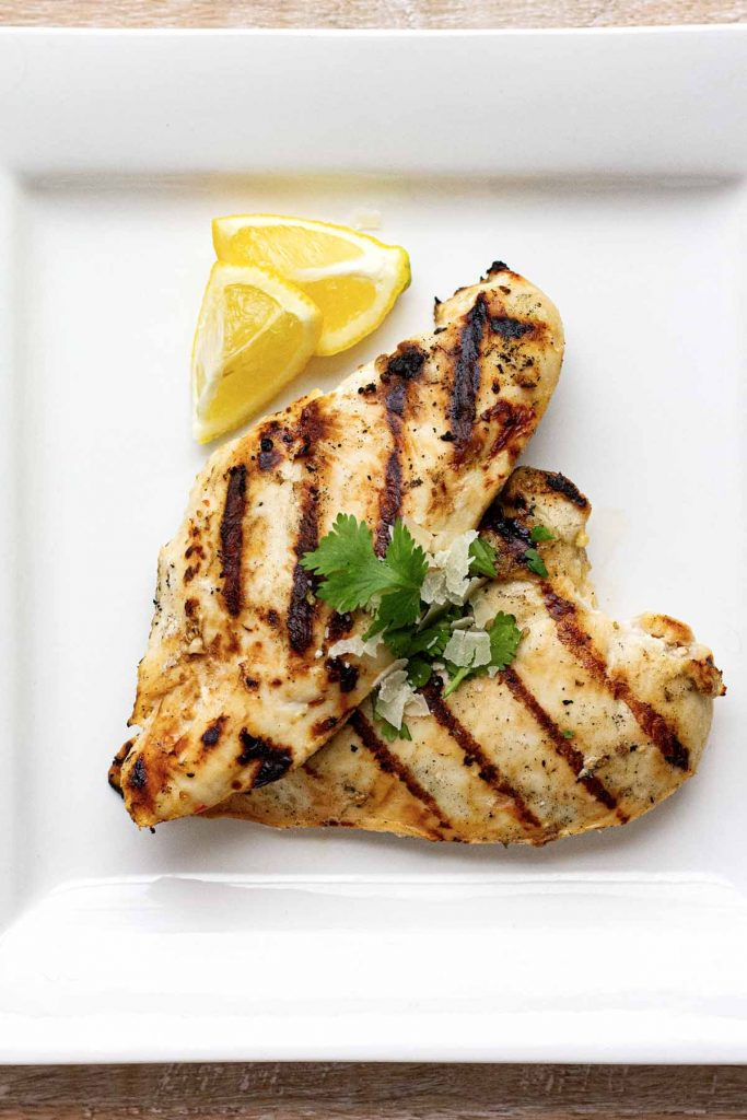 Above shot of grilled chicken on white plate.