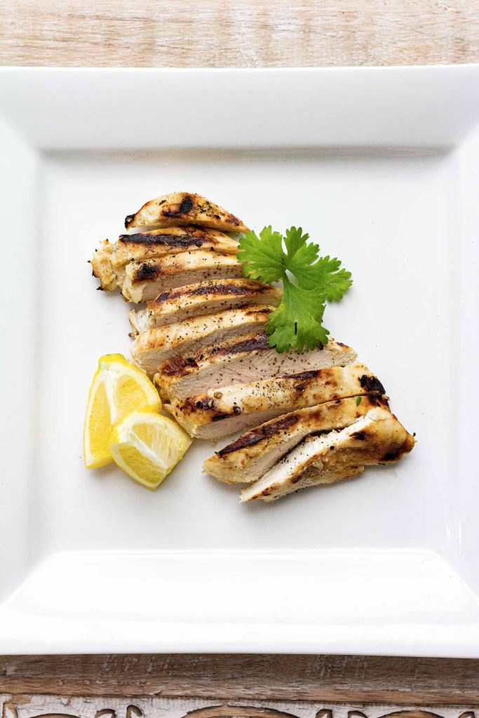 View of sliced chicken on white plate from above.