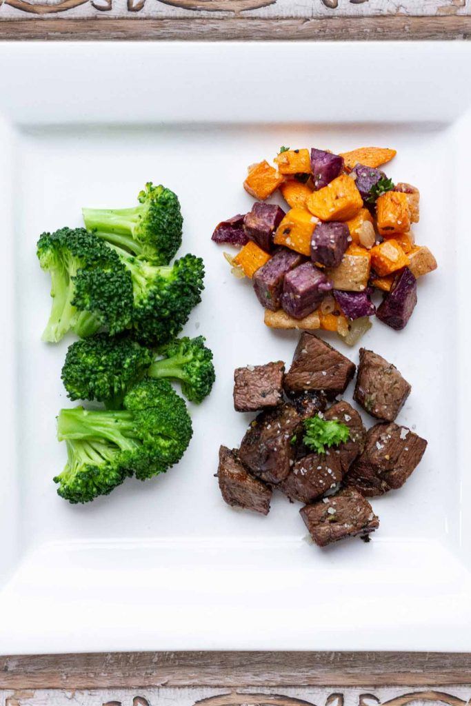 Plate method with broccoli, broiled sweet potato and garlic steak bites on white plate.