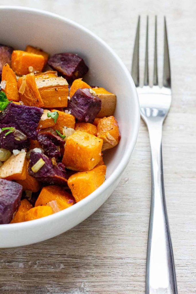 Broiled purple and orange sweet potato bites in white bowl with fork on the side.