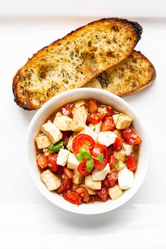 Bruschetta in white bowl with toasted bread on the side.