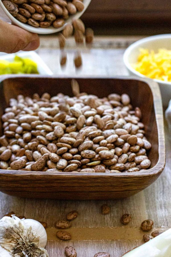 Dry pinto beans bean poured into a wood bowl.