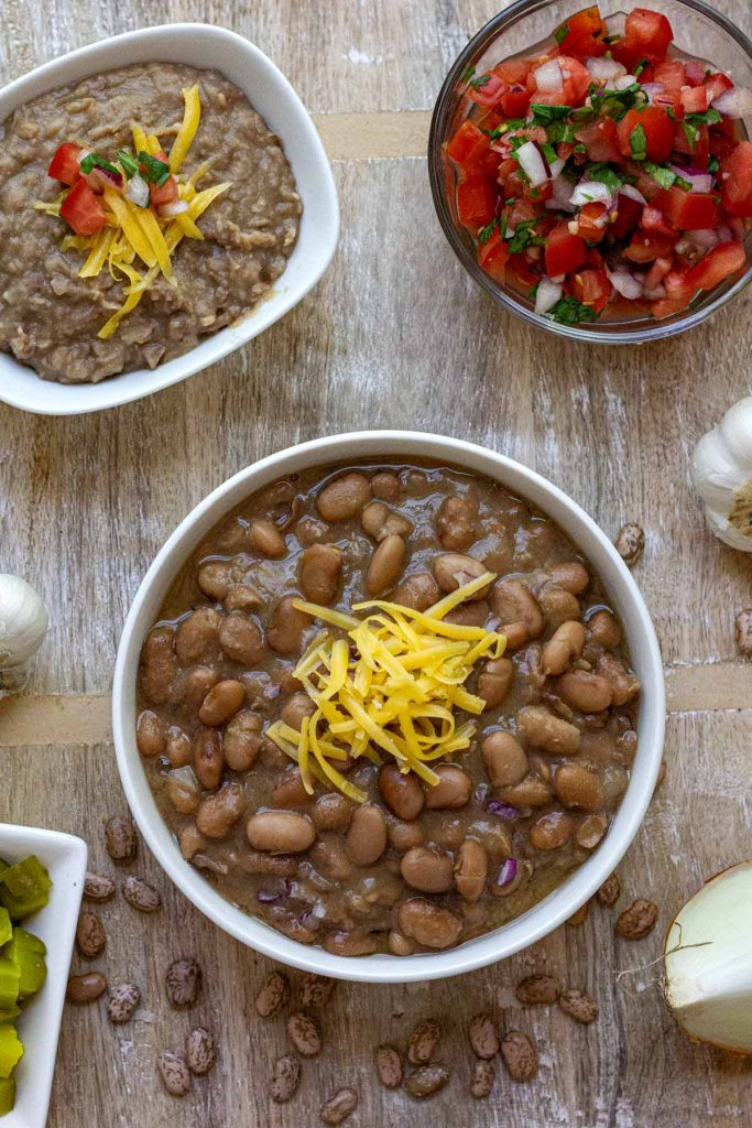 Top view of whole pinto beans in a white bowl topped with cheese with bowls of refried beans and pico de gallo to the side.