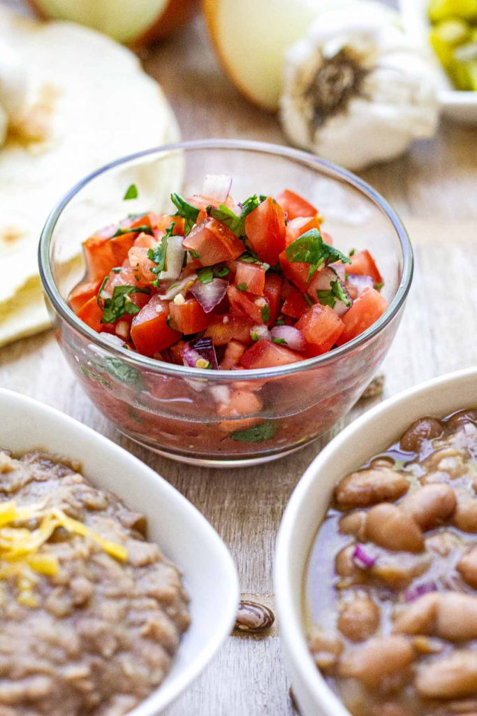 Small clear bowl with pico de gallo with potential sides in foreground and background.