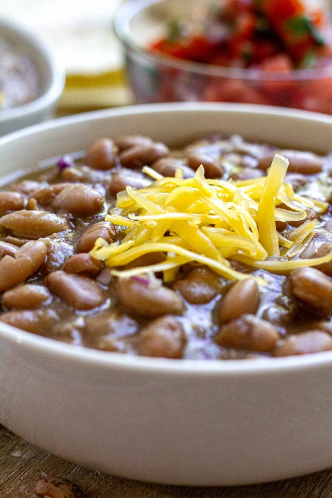 Close up side view of pinto beans in white bowl topped with cheese.