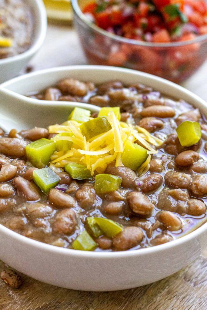 Pinto beans in white bowl topped with pickle and cheese.