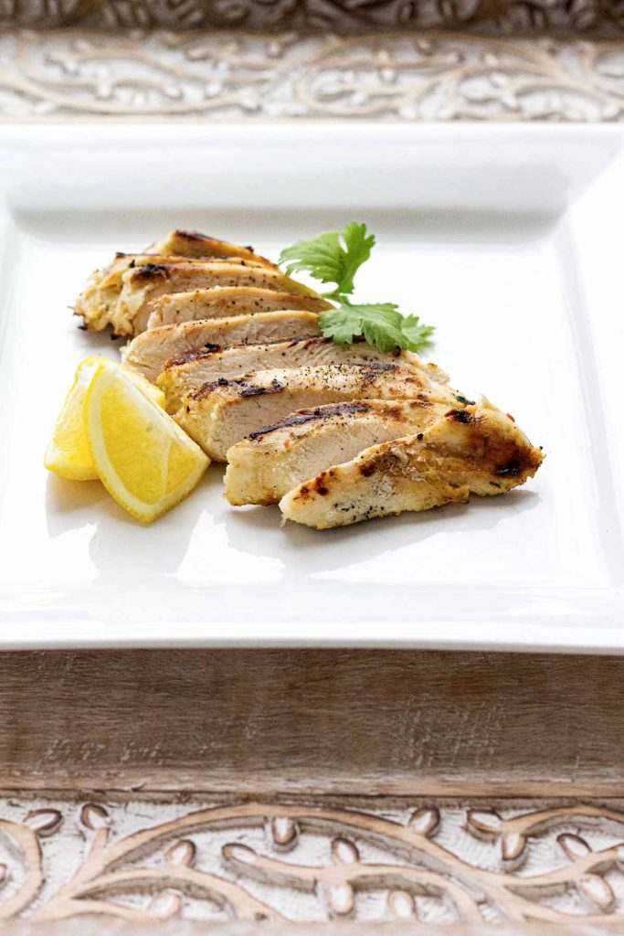 Sliced chicken on white plate with lemon and parsley as garnish.