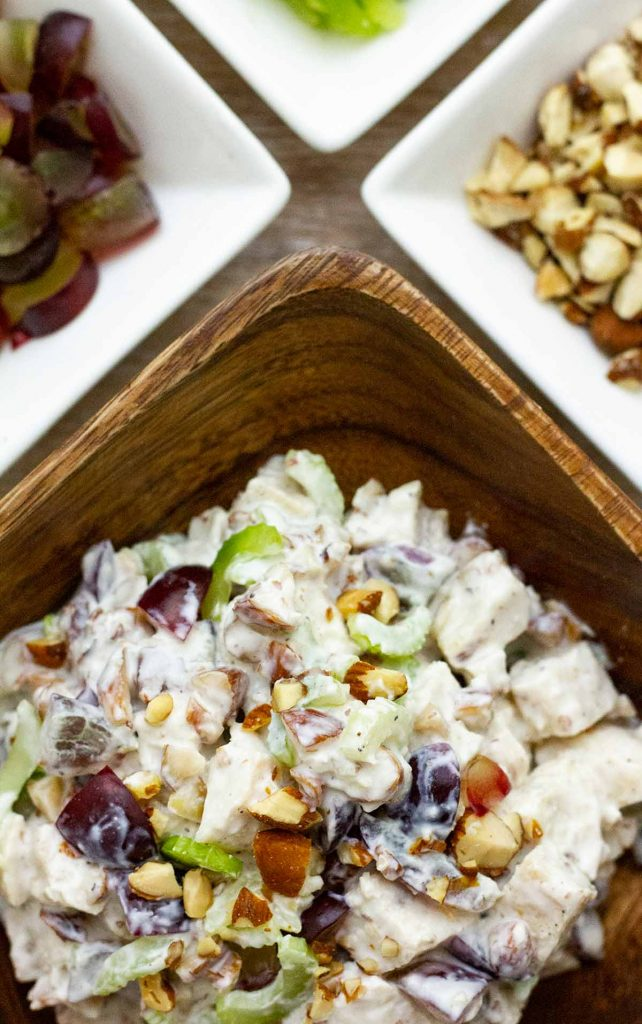 Chicken salad in wooden bowl with surrounding small bowls of ingredients.