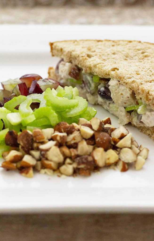 No Mayo chicken salad sandwich on whole wheat bread with nuts, celery, grapes as a side.