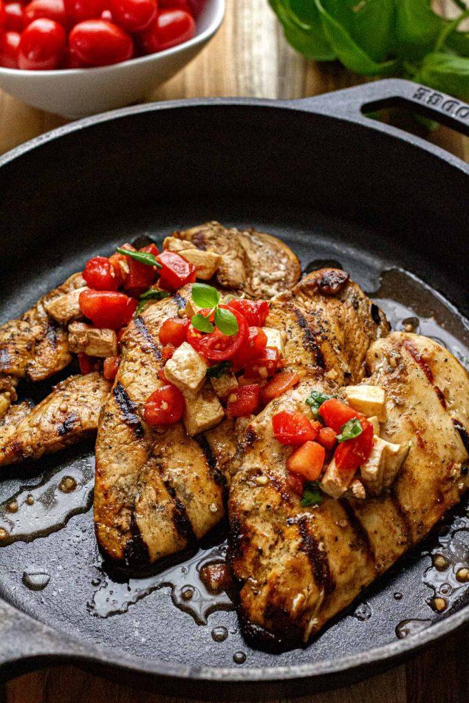 Grilled chicken bruschetta in black iron skillet.