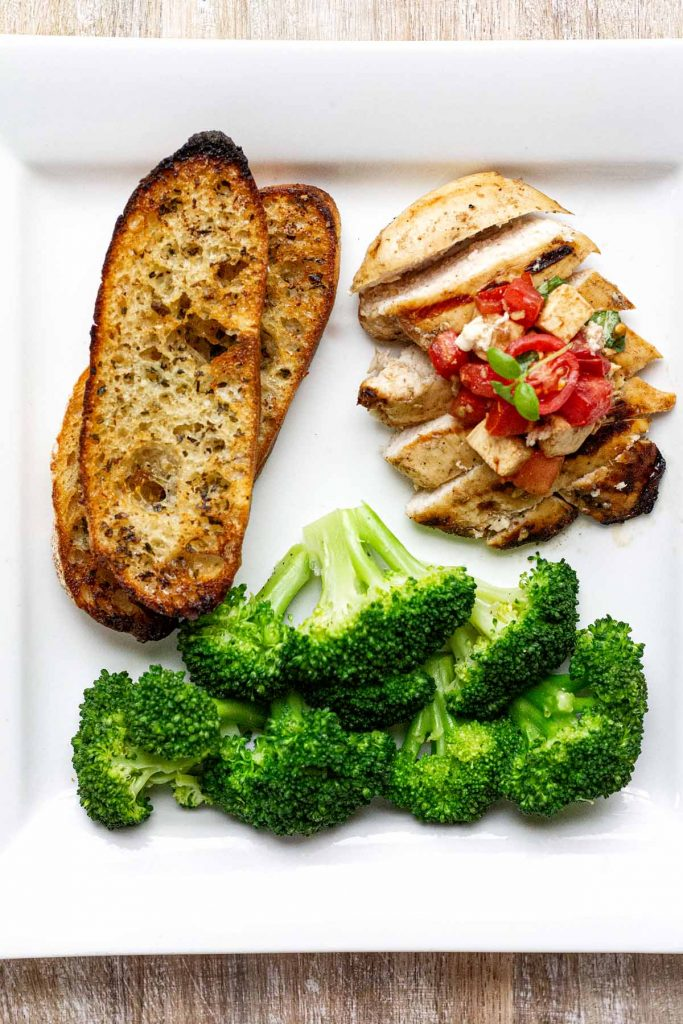 Plate method demonstrated by grilled chicken with bruschetta, garlic toast and broccoli.