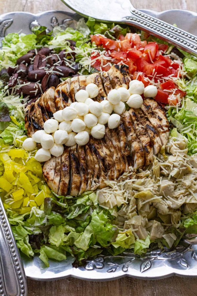 Antipasto salad pictured on silver platter with tongs to the side.