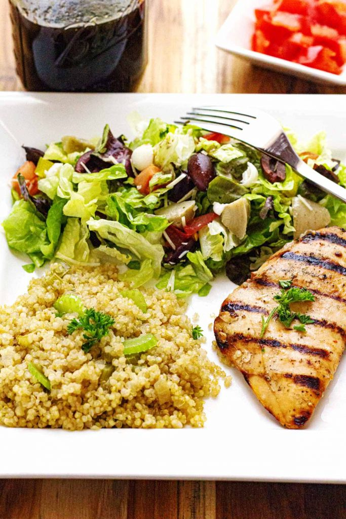 Plate method with grilled chicken, couscous, and salad on white plate.
