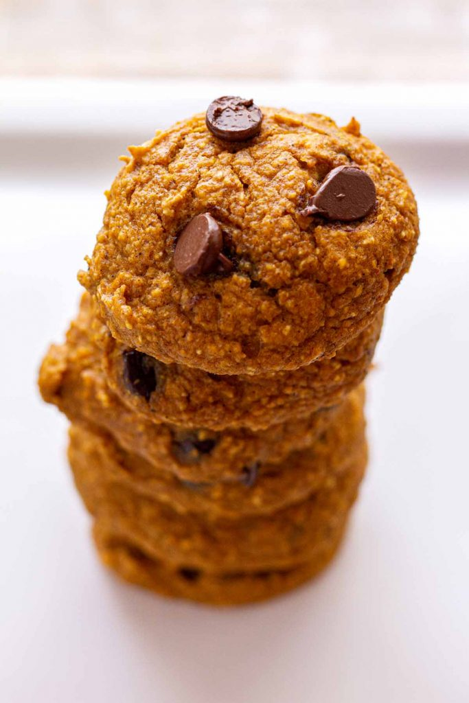 Six Pumpkin Chocolate Chip Cookies stacked on top of each other.