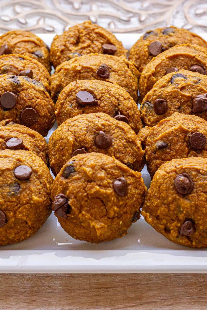 Multiple Pumpkin Chocolate Chip Cookies on a white plate.